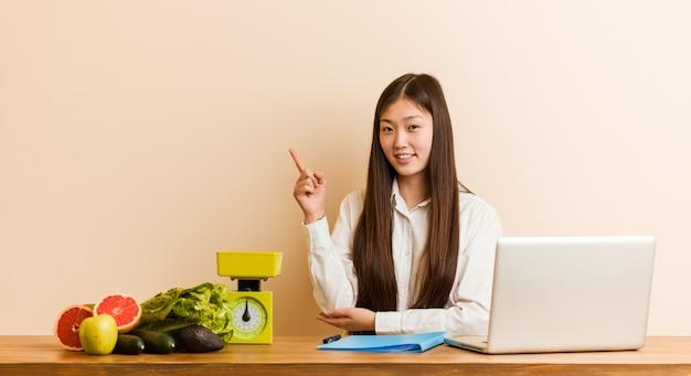 若い栄養士の中国人女性が人差し指で元気に指している笑みを浮かべて彼女のラップトップで働いています。