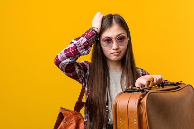 ショックを受けているスーツケースを保持している若いアジア女性、彼女は重要な会議を覚えています。