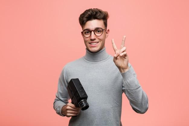 Молодой интеллектуальный человек, держащий фильм, показывая номер два с пальцами.