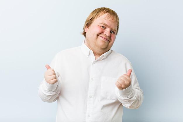 Молодой подлинный рыжий толстяк поднимая оба больших пальца вверх, улыбаясь и уверенно.