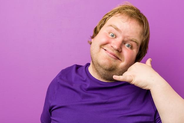 Молодой подлинный рыжий толстый человек, показывая мобильный телефонный звонок жест с пальцами.