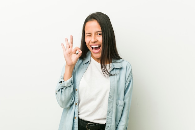若いヒスパニック系女性は目をまばたきし、手でいいジェスチャーを保持します。