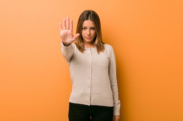 Молодая подлинная харизматическая женщина реальных людей против стены стоя при протянутая рука показывая знак стопа, предотвращая вас.