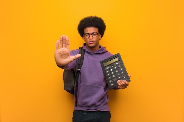 若いアフリカ系アメリカ人学生男の前に手を入れて電卓を保持