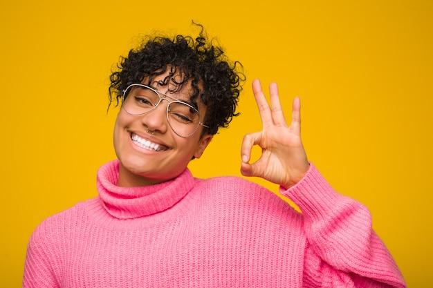 Молодая афро-американская женщина нося розовый свитер подмигивает глазу и держит одобренный жест рукой.