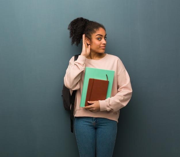 若い学生黒人女性はゴシップを聞いてみてください。彼女は本を持っています。