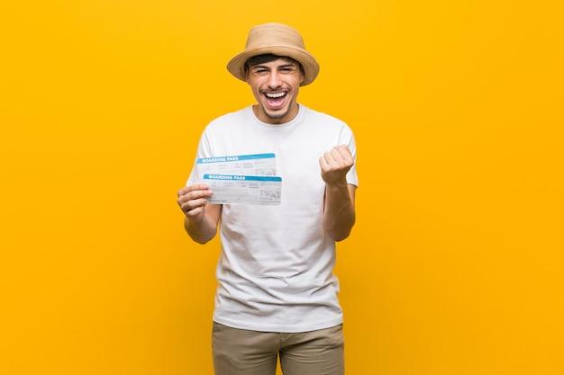 屈託のない、興奮して応援航空券を保持しているヒスパニック青年。勝利 。