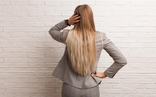 何かを考えて後ろから若いロシアビジネス女性