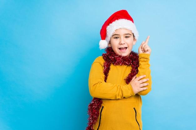 Маленький мальчик, празднование рождества, носить шляпу санта изолированные улыбаясь, весело указывая с указательным пальцем прочь.