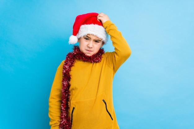 ショックを受けて隔離されたサンタ帽子をかぶってクリスマスの日を祝う小さな男の子は、重要な会議を思い出した。