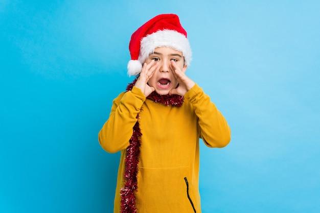 サンタの帽子を身に着けているクリスマスの日を祝っている小さな男の子は叫んで前に興奮していた。