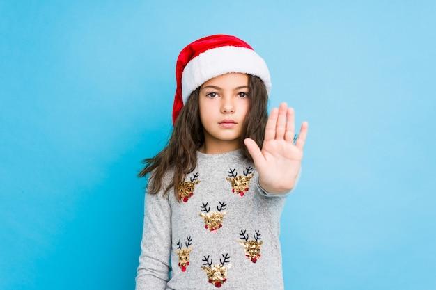 Маленькая девочка празднуя рождество стоя при протягиванный знак стопа показа руки, предотвращая вас.