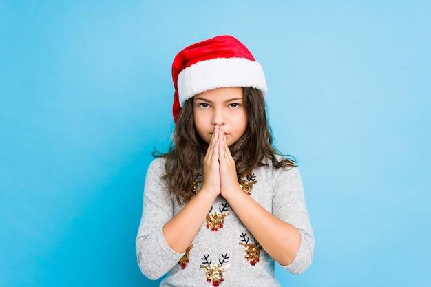 口の近くで祈って手を繋いでいるクリスマスの日を祝っている少女は、自信を持って感じています。