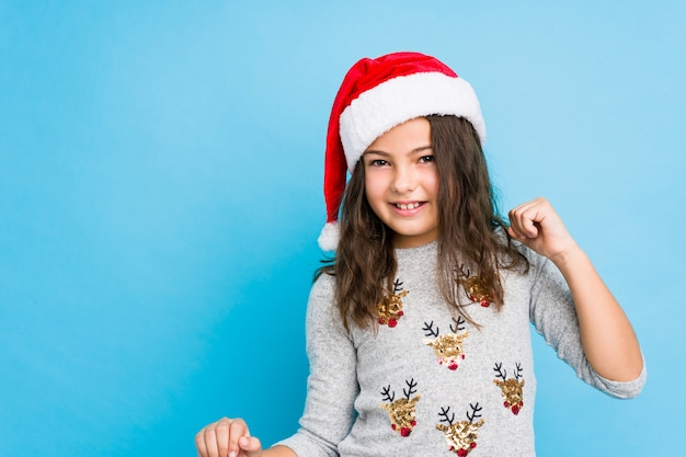 Маленькая девочка празднует рождество танцевать и веселиться.