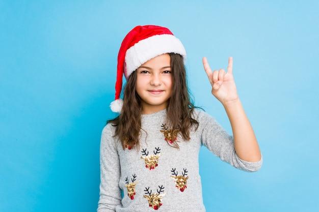 Маленькая девочка празднуя рождество показывая жест рожков как концепция революции.