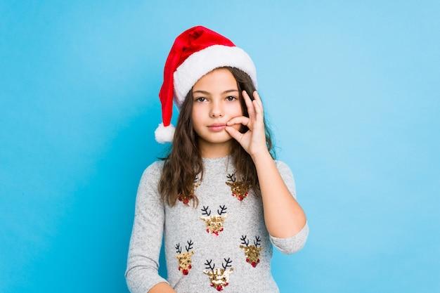秘密を守る唇に指でクリスマスの日を祝う少女。