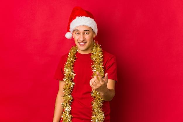 Молодой человек на рождество, указывая пальцем на вас, как будто приглашая подойти ближе.