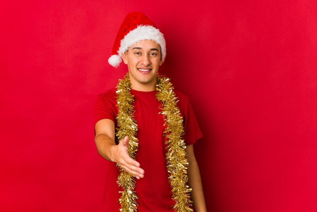 ジェスチャーの挨拶でカメラに手を伸ばしてクリスマスの日に若い男。