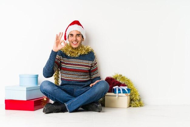 クリスマスの日に腕を伸ばして、リラックスした位置に若い男。