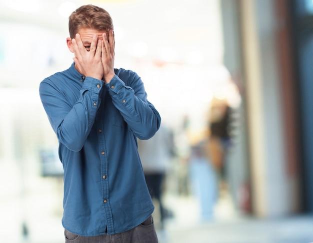 両手で顔を覆っている男