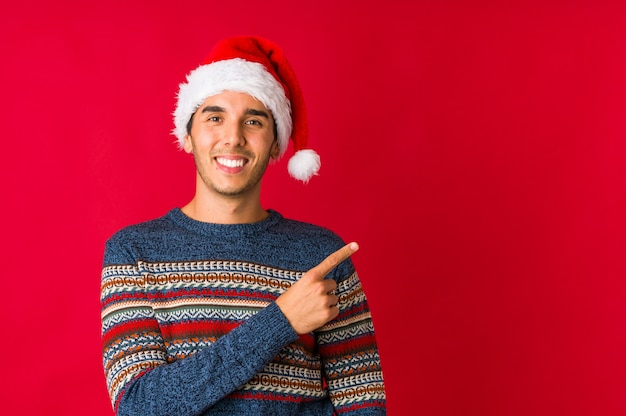 クリスマスの日の笑顔と親指を上げる若い男