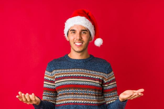 クリスマスの日の幸運のための指を交差の若い男