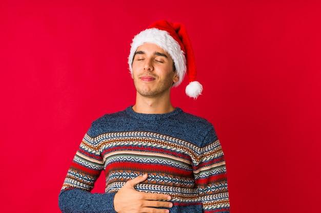 Молодой человек на рождество, охватывающих уши руками, стараясь не слышать слишком громкий звук.