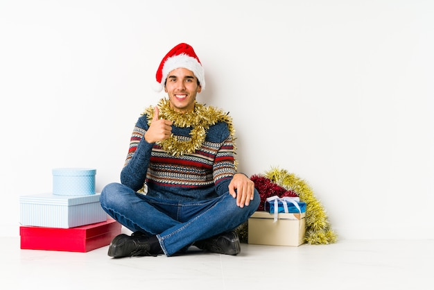 Молодой человек на рождество громко смеется, держа руку на груди.