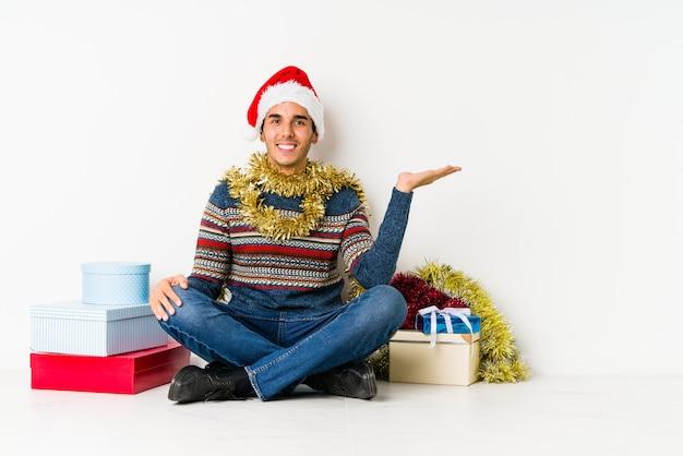 親指アップとクリスマスの日に若い男は、何かについて乾杯、サポートし、概念を尊重します。