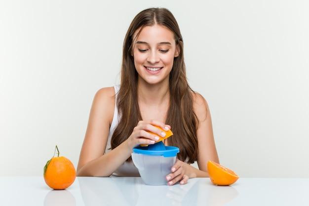 オレンジジューサーを保持している若い白人女性