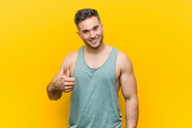 若いフィットネス男笑顔と親指を上げる