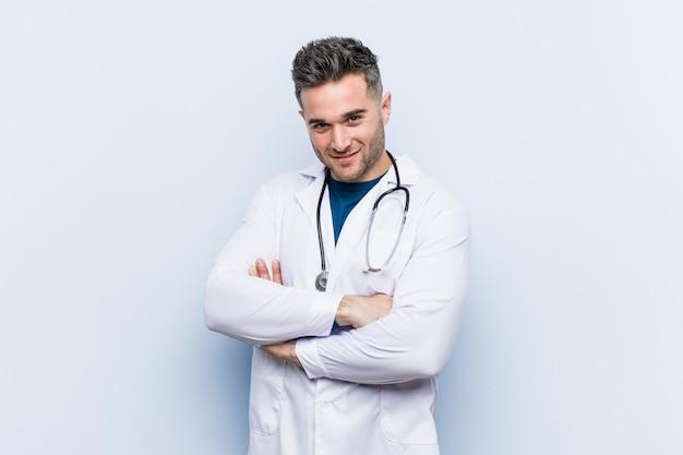 Молодой красивый врач мужчина, который чувствует себя уверенно, скрестив руки с решимостью