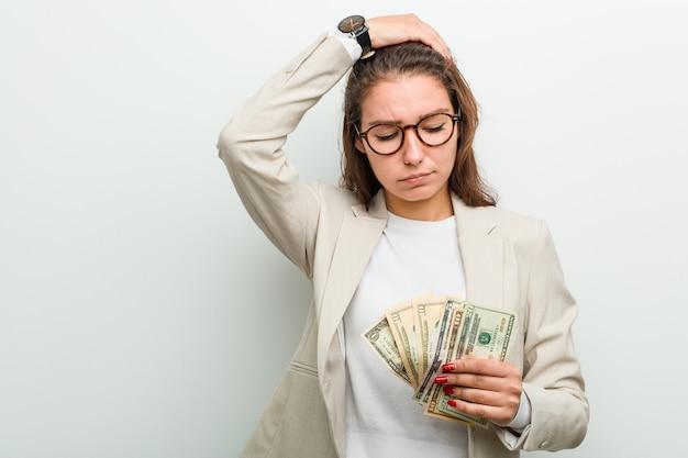 ショックを受けているドル紙幣を保持している若いヨーロッパビジネス女性、彼女は重要な会議を思い出した