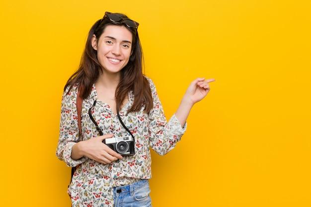 人差し指で元気に指している笑顔若いブルネット旅行者女性