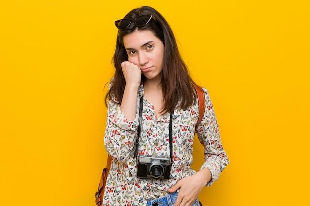 悲しいと物思いにふける若いブルネット旅行者女性