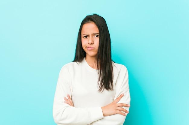 皮肉な表情でカメラで見て不幸な若いかなりヒスパニック系女性