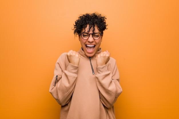 Молодая смешанная женщина афроамериканца против коричневой предпосылки