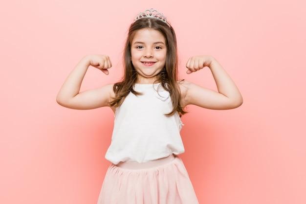 腕で強さのジェスチャーを示すプリンセスの外観を着ている少女