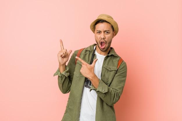 Молодой филиппинский путешественник мужчина, указывая указательными пальцами на копию пространства, выражая волнение и желание