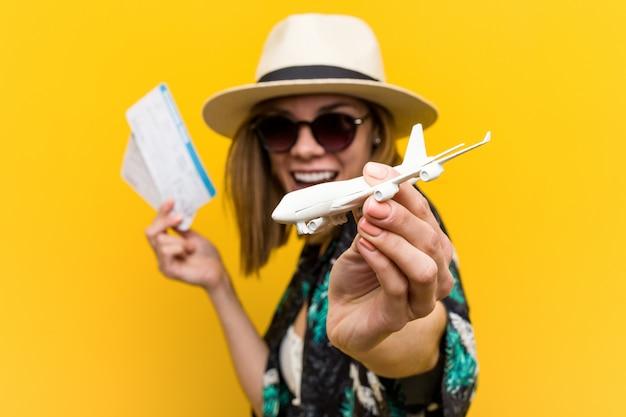 Молодая кавказская женщина держа авиабилеты очень счастливые