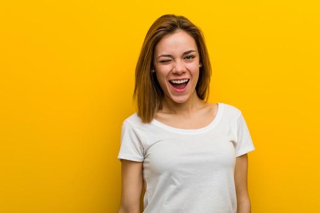 Молодая натуральная кавказская женщина подмигивает, веселая, дружелюбная и беззаботная