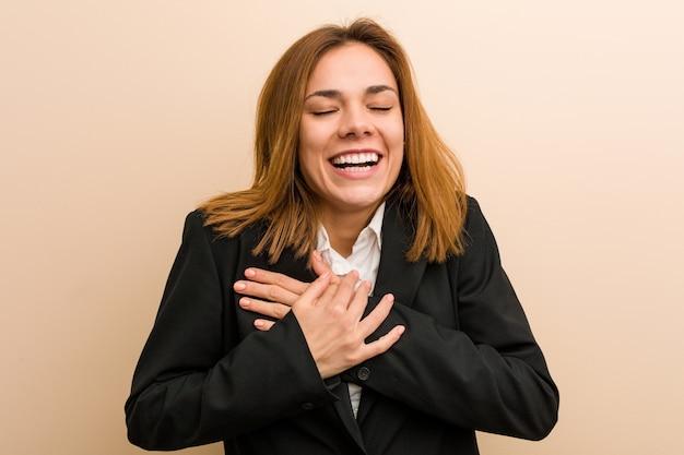 Молодая кавказская бизнес-леди смеясь держащ ее руки на сердце