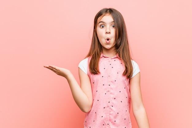 Милая маленькая девочка произвела впечатление держа космос экземпляра на ладони