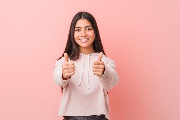 親指アップとカジュアルなスポーツの外観を身に着けている若いかなりアラブの女性、何かについて乾杯