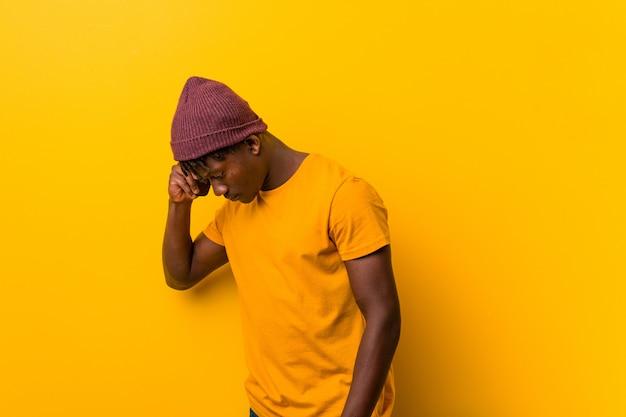帽子をかぶっていると電話を使用して立っている若いアフリカ人