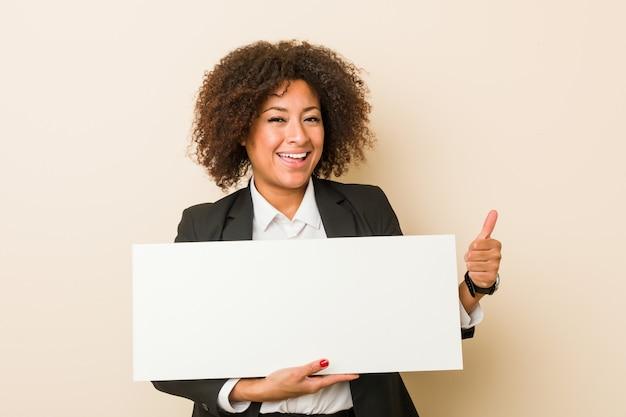 Молодая афро-американская женщина держа плакат усмехаясь и поднимая большой палец руки вверх