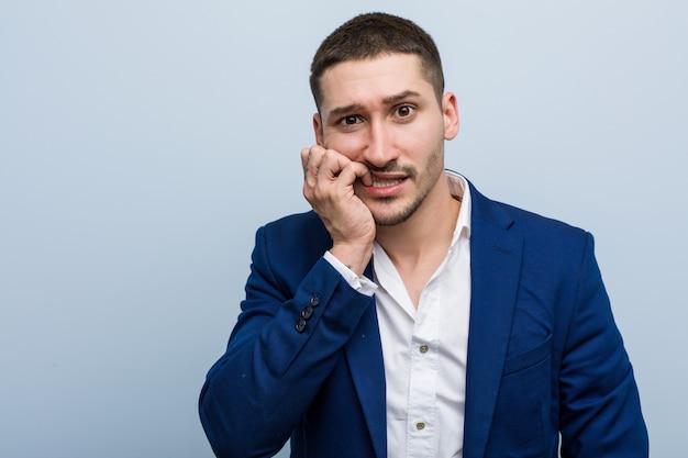 Молодой деловой кавказский человек кусает ногти, нервничает и очень беспокоится