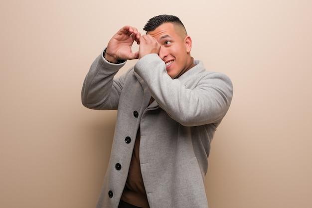 Молодой латинский бизнесмен делая жест подзорной трубы