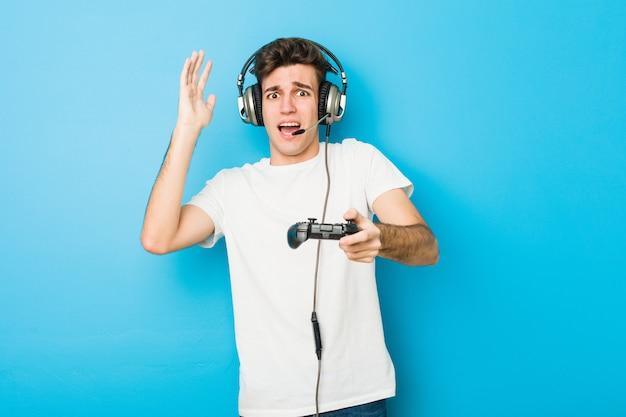 Подросток кавказский человек, используя наушники и игровой контроллер