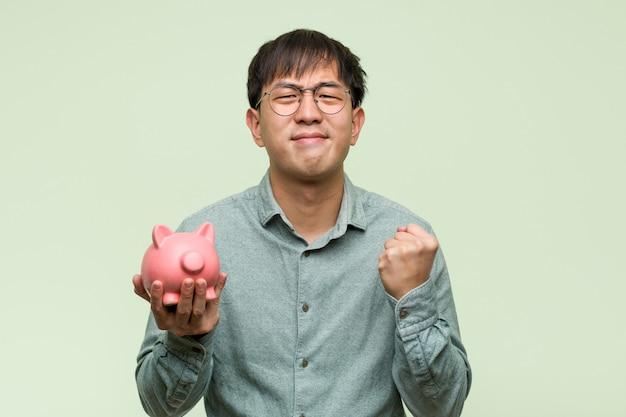 Молодой азиатский человек держа копилку удивленный и сотрясенный